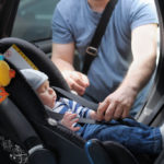 Father-straping-baby-in-car-seat